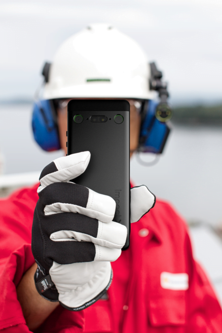 Intrinsically Safe Cell Phone Impact X Bartec front operator red shirt gloves on Explosion proof Camera taking pictures