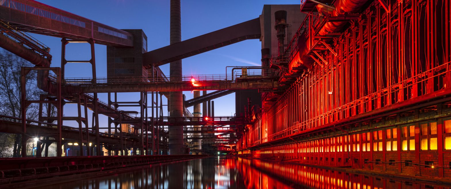 Banner picture of a refinery in the evening introducing the article topic